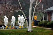 A decontamination crew dressed in hazardous material suits stands together as an investigator takes photographs outside Ottilie Lundgren's Oxford, Conn., home. The house was declared a crime scene Friday. Lundgren, 94, died of inhalation anthrax Nov. 21. Lundgren's mail may have been contaminated by anthrax letters sent to senators in Washington.