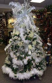 Themed Christmas trees, like this white tree adorned in feathers and silver accents, offer a change of pace from more traditional holiday trees.