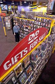 DVD movies fill the display at a Blockbuster store in Palo Alto, Calif. Stores like Blockbuster are devoting more room to rental DVDs as sales of the players climb.