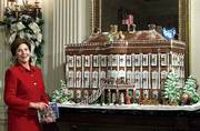 First lady Laura Bush shows off the White House gingerbread house, a replica of the White House as it looked in 1800. Heightened security after the terrorist attacks will keep the White House and its lavish holiday decorations closed to all but invited VIPs. Mrs. Bush is instead taping a video tour of all the glitter to be shown at the nearby White House Visitors Center.