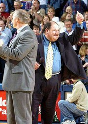 New Ku football coach Mark Mangino, right, acknowledges the Allen Fieldhouse crowd. Mangino was introduced to the Kansas faithful by KU athletics director Al Bohl, left, at halftime of KU's 83-76 victory over Wake Forest on Tuesday.