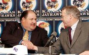 Newly hired Kansas football coach Mark Mangino, left, is congratulated by KU athletics director Al Bohl. Mangino was introduced to the media Tuesday during a press conference.
