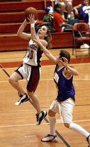 Lawrence High guard Leigh Debiasse drives past Kansas City Harmon's Jenessa Frank for a layin on Tuesday at LHS. The Lions won the girls basketball contest, 78-18.