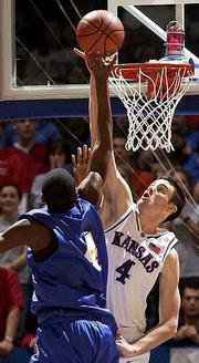 Ku's Nick Collison (4) blocks a shot by Marcus Golson.