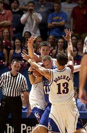 Kansas' Jeff Boschee (13) and Nick Collison sandwich UMKC's Matt Suther. The Jayhawks held on to beat the 'Roos, 79-68, on Saturday night at Allen Fieldhouse.