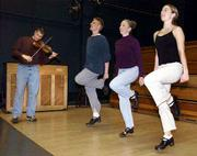 With fiddle music provided by Dan Grotewohl, student Jeff Potter, second from left, and Christine Scott, right, rehearse an Irish step dance with instructor-choreographer Jean Denney in Robinson Center at Kansas University.