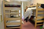 City Center hostel housekeeper Eva Alanis changes the linen in one of the dormitory style rooms. Hostels are ideal lodging for people who enjoy getting to know others.