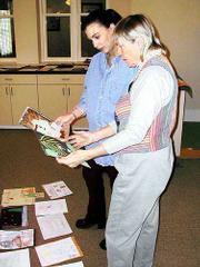 Judges Ellen Casagrande, left, and Jan Gaumnitz look through entries in the Journal-World Holiday Art Contest.