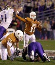Texas quarterback major applewhite throws a pass over Washington's Ben Mahdavi. Texas rallied to win the Holiday Bowl on Friday night at San Diego.