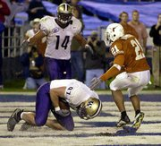Washington's Joe Collier drops to his knees to haul in a touchdown pass. Texas defender Roderick Babers (21) arrived too late Friday night in San Diego. Washington's Jerramy Stevens (14) is also pictured.