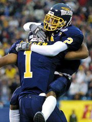 Toledo's Carl Ford (2) hugs Tavares Bolden (1) after Bolden's 28-yard touchdown run. Toledo defeated Cincinnati on Saturday in the Motor City Bowl at Pontiac, Mich.