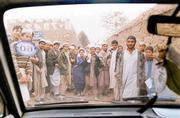 A group of Afghan students at the United Nations-sponsored Eagle Eye School for the Sciences for Displaced Afghan Youth crowd around as Smith's vehicle backs away from the school grounds.