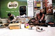 A man proud of his resemblance to Osama bin Laden shines shoes at Aabpara Market in Islamabad, Pakistan, more than a week before his terrorist double was last detected alive at the Tora Bora cave complex, alive and possibly fleeing toward Pakistan.