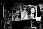 A Peshawar Saddar Bazaar market stall sells tribute posters to the destruction of New York on Sept. 11 and its architect, Osama bin Laden along with Indian fashion posters.