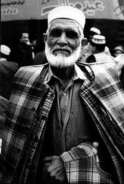 A sport coat merchant poses for a portrait as he makes his rounds through the Saddar Bazaar in Peshawar.