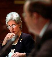 Kansas Insurance Commissioner Kathleen Sebelius, left, listens to