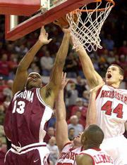 Oklahoma's Aaron McGhee (13) shoots over Nebraska's John Turek (44), Ross Buckendahl, center bottom, and Brennon Clemmons. The Sooners beat NU, 78-51, on Wednesday in Lincoln, Neb.