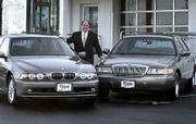 Steve Kalafer, who owns auto franchises in New Jersey, bridges the gap between a 2002 540 BMW, left and a 2002 Grand Marquis, right. Boomers like cars like the BMW while their parents bought cars like the Grand Marquis when they achieved financial security.