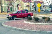 Vehicles slow down but keep moving at the traffic circle at Eighth and Michigan streets, some neighborhood residents say. The circle and its full-sized counterparts Lawrence's four roundabouts have served their intended purpose of calming traffic, city officials say.