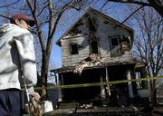 Derek Hein, One of four residents who escaped an early-morning house fire on Ohio Street, surveys the damage to his rental house. Hein, who injured his ankle jumping from a second-floor awning, was awakened to the Friday fire by his barking dog, Aiko, who died in the fire.