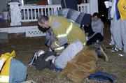 A Lawrence-Douglas County firefighter tends to a victim of an early-morning fire at 1216 Ohio. Three residents had to jump from the house to escape the fire Friday.