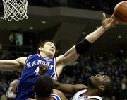 Ku's Nick Collison (4) stretches to grab a rebound as Texas A&M's Keith Bean looks on. The Jayhawks beat the Aggies, 86-74, on Saturday in College Station, Texas.