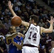 KU's Drew Gooden, left, fires a pass around Texas A&M's Tomas Ress. The Jayhawks dropped the Aggies, 86-74, on Saturday in College Station, Texas.