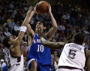 Kansas' Kirk Hinrich (10) shoots between Bernard King, left, and Nick Anderson. Hinrich finished with 15 points.