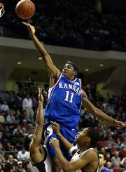 Ku's Aaron miles (11) glides in for two of his 10 points against Bradley Jackson, left, and Bernard King.