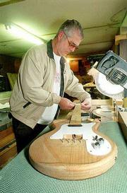 Ray Brookover of Poplar Bluff, Mo., works on one of his handcrafted custom guitars. Brookover makes custom guitars for friends and family members but hopes to turn his hobby into a lucrative business in the future.