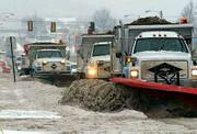 A string of city snow plows loaded down with sand travels up and down Iowa Street, clearing piles of snow from the roadway.