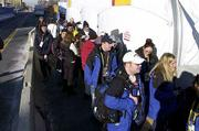 People wait in the cold to gain access to the Media Center Friday in Salt Lake City. The security checks have caused queues to form outside the Media Center due to their stringency. The Salt Lake City Winter Olympic Games and their 375.5 hours of TV coverage begin Friday.