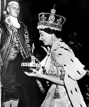 Elizabeth II wears the bejeweled Imperial Crown and carries the Orb, in left hand, and Scepter with Cross as she leaves Westminster Abbey on June 2, 1953, at the end of her coronation ceremony. Elizabeth inherited the British throne on Feb. 6, 1952, upon the death of her father, King George VI.