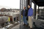 Jeff Shmalberg, left, and Martin Moore, partners in the Downtown 2000 project, survey the view from the fourth floor of their latest construction project at the northwest corner of 10th and New Hampshire streets. The building will include city offices, retail space and two floors of apartments.