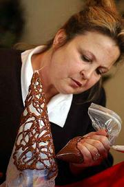 Christy Carlisle makes a chocolate lace cone by squeezing warm chocolate ribbons onto a wax paper cone. Once the chocolate has set, she peels the paper away from the inside of the cone.