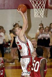 Lawrence High's David Parkinson, left, launches a shot as Kansas City Wyandotte's Lawrence Franklin (50) looks on. The Lions snared a 57-56 victory Tuesday night at LHS.