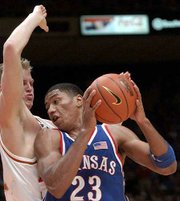 Kansas' Wayne Simien (23) drives on Jason Klotz. Simien had 17 points and 10 rebounds Monday in Austin, Texas.