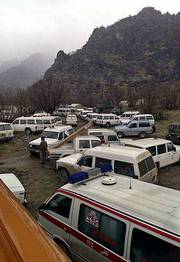 Dozens of ambulances and cars belonging to Iran's Red Crescent remain parked at the foot of the Sefid Kouh mountains where a plane crashed on Tuesday. All 118 passengers and crew on board the plane are believed dead.