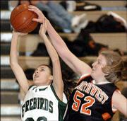 Free State's Ramona Daney, left, attempts to shoot against SM Northwest's Mandy Smith. The Firebirds lost, 61-25, Friday night at Free State.