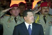 Venezuelan President Hugo Chavez listens to the national anthem during a civil and military parade at La Victoria, about 60 miles east of Caracas, Venezuela. Venezuelan Air Force Col. Pedro Soto and National Guard Cap. Pedro Flores stunned the nation last week by demanding that Chavez resign and new elections be held.