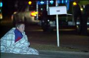 Eight-year-old Jerry Ratcliff watches the activity of firefighters as they work in teams to extinguish the flames in an apartment building near 24th and Missouri streets. One resident of the Coach Light Apartments, Janet Murphy, died in the fire. More than 20 people who lived in the building were left without a home.