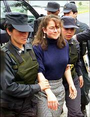 Escorted by police, Lori Berenson, center, returns to the safehouse that she shared with leftist rebels who police say were plotting to attack Congress, in Lima, Peru, in this Oct. 20, 2000, file photo. Peru's Supreme Court has upheld a 20-year prison sentence against Berenson for collaborating with leftist rebels to seize Congress, the presiding justice said Monday.