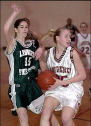 Free State High School's Kelsey Schelar, left, defends against Lawrence High School's Liz Hyler in the first half of their sophomore basketball game at LHS. A proposal to eliminate sophomore sports, like Monday night's game, is being discussed by the Lawrence school board as a means to save money.