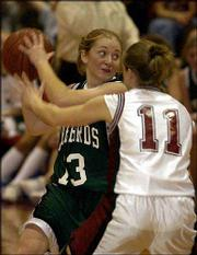 Free State's Julie Seidel, left, keeps the ball away from Lawrence's Ashley Burnett. The Lions beat the Firebirds, 52-42, on Monday at LHS.