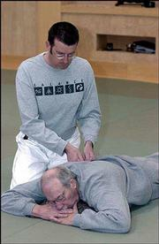 Charles Ross gives Jed Davis a massage during a Ki-Aikido class.