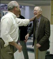 Larry Midyett, left, a former choir member congratulates R. Wayne Nelson after going through the receiving line. Former students and education associates honored the 90-year-old Lawrence resident with a surprise birthday party Sunday at Lawrence High School. A plaque with Nelson's likeness was unveiled and will be placed outside an LHS music room to be named for him.