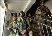 Israeli army soldiers hold a position inside a Palestinian house at the border of the Balata refugee camp, in the West Bank town of Nablus. Israeli troops, backed by tanks and helicopter gunships, launched a major assault on this West Bank refugee camp early Thursday. Since the operation began, 19 Palestinians and two Israeli soldiers have been killed.