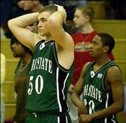 Free State's cole douglas, left, and Andron Cruse are dejected following the Firebirds' loss to Olathe East. The Firebirds fell, 53-52, to Olathe East in the sub-state semifinals Friday night at FSHS.