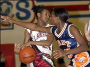 Lawrence's Audrey Pope, left, tangles with Olathe East's Tamara Vincent. The Hawks beat the Lions, 52-39, on Saturday at Free State High.