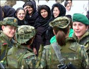 A group of four Afghan women watches a group of four female Spanish International Security Assistance Force peacekeepers during International Women's Day festivities at The Ministry of Women's Affairs, in Kabul, Afghanistan. Friday was the first time in 11 years that International Women's Day was celebrated in Afghanistan.